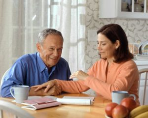Adult woman sitting at a kitchen table with elderly man