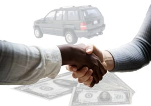 Two hands shaking with a car and money in the background